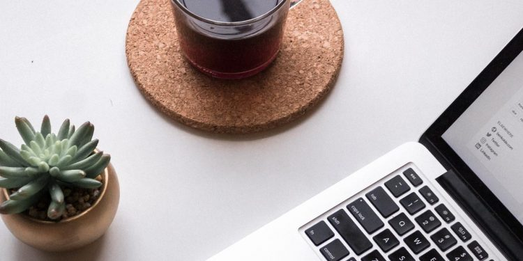 Photo of a laptop and cup of coffee on a table.